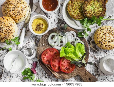 Ingredients for cooking vegetarian burgers - zucchini burgers homemade buns tomatoes onions herbs spices and sauces on a light stone background. The view from the top