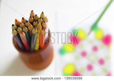 Some color pens on a table next to a mandala book for adult. Mindfulness activity. Empty copy space for editor's text.