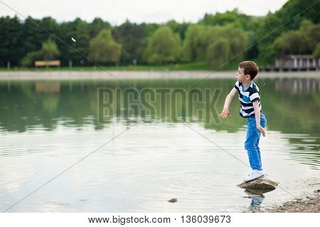 active boy throws small stone into the lake