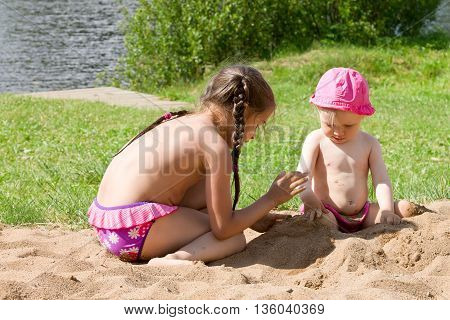 Children on the beach by the river. Two little girls, two sisters playing in the sand on the beach