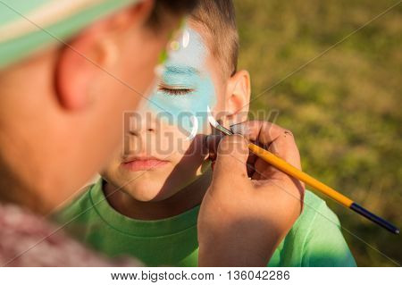 Woman does greasepaint on the child's face
