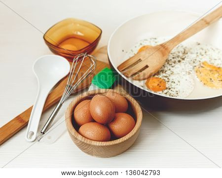 Fried eggs in the frying panbreakfast ingredients.kitchen accessories.Fresh Brown Eggs in the Wooden Plate.Cooking morning food.White table.Selective Focus