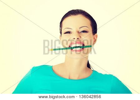 Thoughtful woman biting pencil