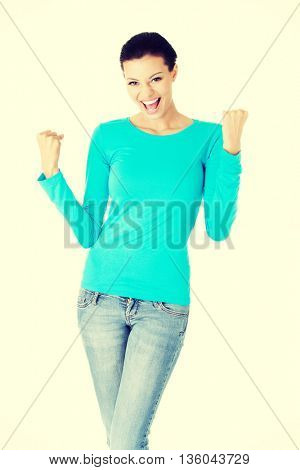 Excited happy young woman with fists up