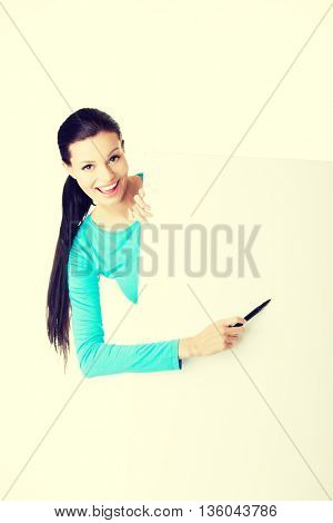 Woman writing with a pen on blank board.