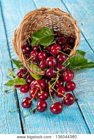 Fresh cherry pile in basket with leaves placed on old wooden planks