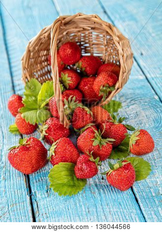 Fresh strawberry pile in basket with leaves placed on old wooden planks