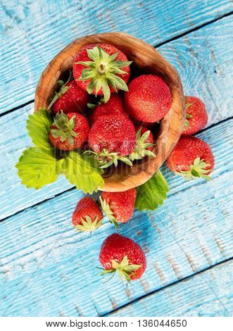 Fresh strawberry pile in bowl with leaves placed on old wooden planks. Shot from aerial view