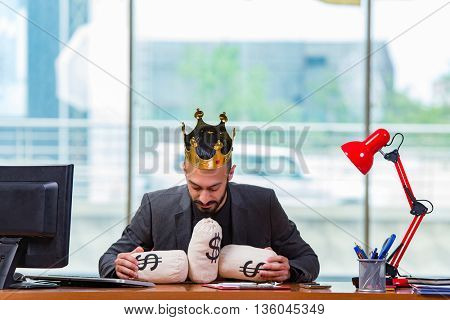 Businessman with crown and money sacks in the office