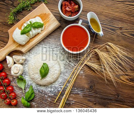 Pizza dough with ingredients and tomato sauce served on rustic wooden table. Aerial shot, copyspace for text