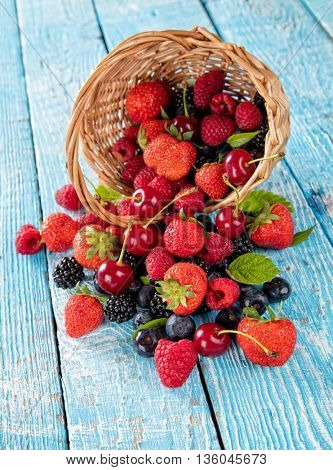 Fresh berry fruit pile in basket with leaves placed on old wooden planks