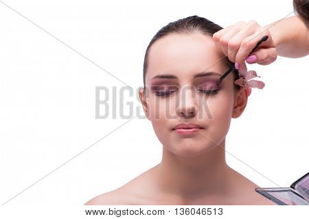 Beautiful woman during make-up cosmetics session isolated on whi