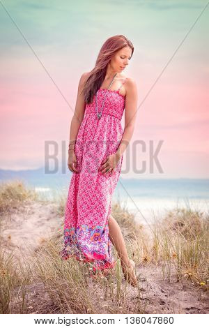 Beautiful woman wearing pink dress at beach