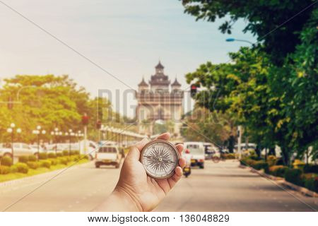 Hand man holding compass on road Victory Gate Patuxai Vientiane Laos Southeast Asia