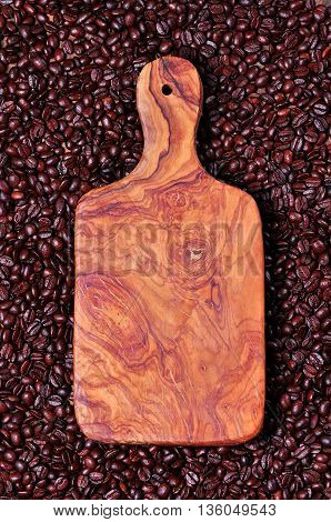 Cutting board of olive wood on the background of coffee beans