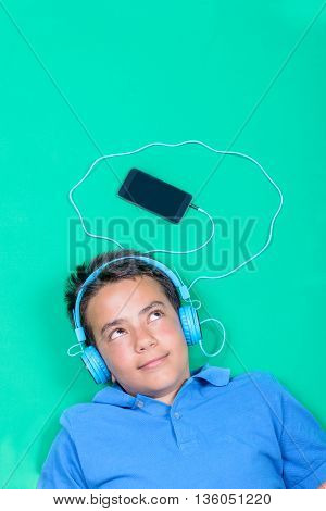 teenager listening to music with headphones over green background.