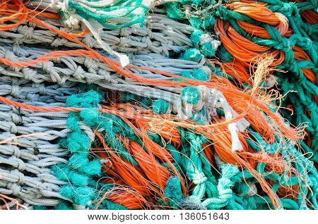 Closeup of a bunch of colorful knotted fishing nets ropes and lines on the dock of a Dutch fishing port on a sunny day in spring.