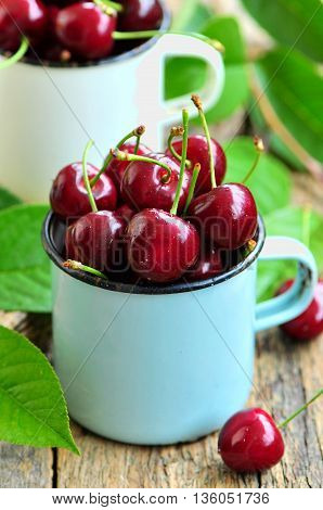 Fresh organic cherries on the old wooden background.