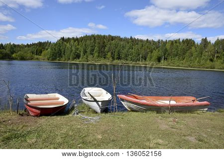 Three small plastic boats on the shore in a little lake in the North of Sweden.