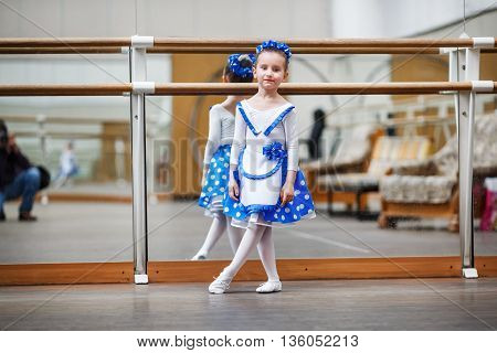 Little girl dancer posing in studio with wooden floors on the background of mirrors. Little ballerina. Shallow depth of field. Selective focus.
