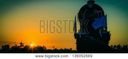 Silhouette steam locomotive at sunset. Vintage tone. Cinema style.