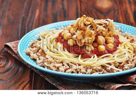 Kushari - Egyptian dish of lentils, rice, pasta, chickpeas with tomato sauce and crispy onions