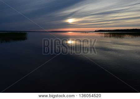 Sunbeam at sunset in the summer on the water surface of the lake