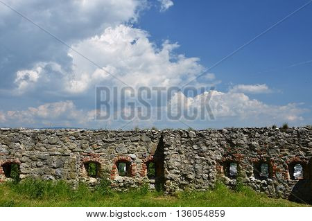 The walls of the castle with a background of blue sky and clouds.