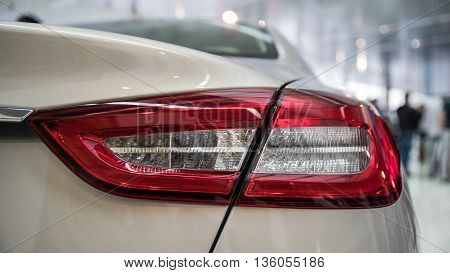 Detail on the rear light of a white car