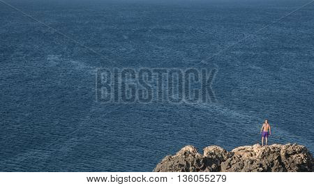 Unrecognized man standing at the edge of a rock ready to jump on the deep blue sea.