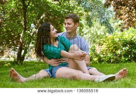 Romantic couple sit on grass in city park, summer season, lovers boy and girl