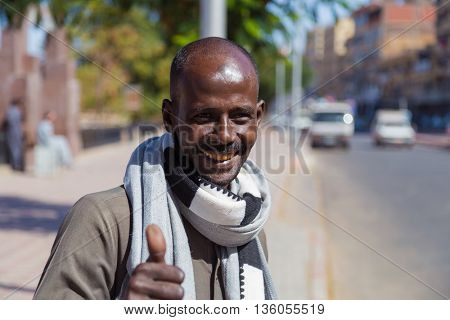 ASWAN, EGYPT - FEBRUARY 6, 2016: Portrait of smiling local man showing thumbs up.