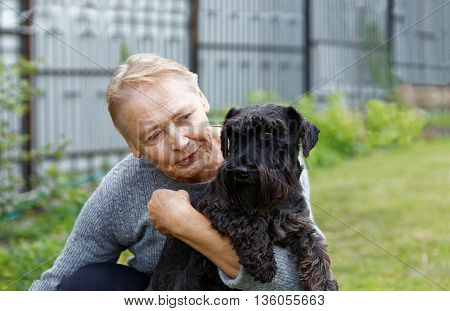 Portrait of an old woman holding black dog Zwergschnauzer