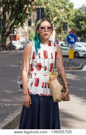 MILAN ITALY - JUNE 21: Fashionable woman poses outside Armani fashion show building during Milan Men's Fashion Week on JUNE 21 2016 in Milan.