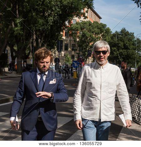 MILAN ITALY - JUNE 21: Fashionable men pose outside Armani fashion show building during Milan Men's Fashion Week on JUNE 21 2016 in Milan.