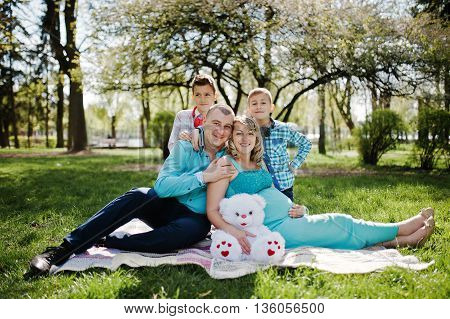 Happy Pregnant Couple With Two Sons Hugging And Sitting On Plaid Background Spring Nature