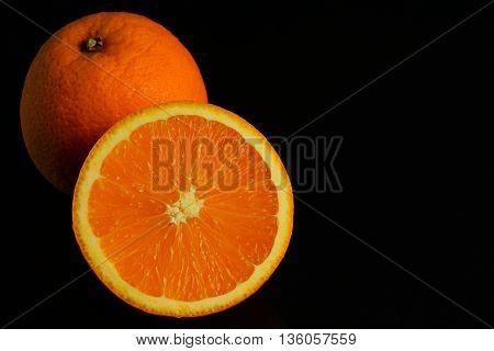 Oranges Split half on dark background with copy space