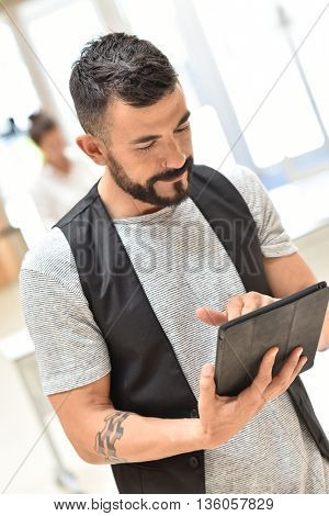 Trendy guy in office websurfing on tablet