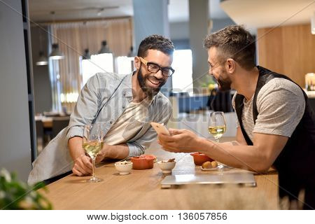 Trendy guys in bar drinking wine and using smartphone