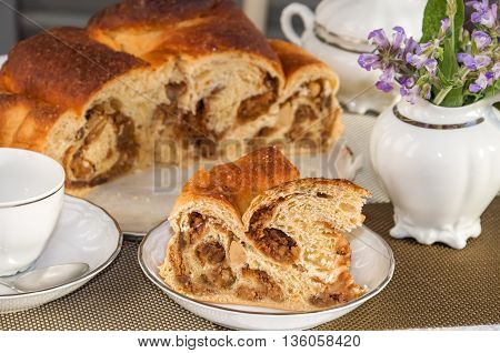 Good piece of typical italian flavorous home baked cake La Gubana with sophisticated stuffing (hazelnuts fruit chocolate walnut raisins honey etc.) with purple flowers of salvia on the table covered for tea. Traditionally bake for Christmas and Easter.