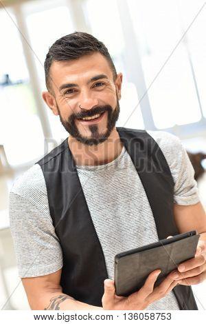 Trendy guy in office websurfing on tablet