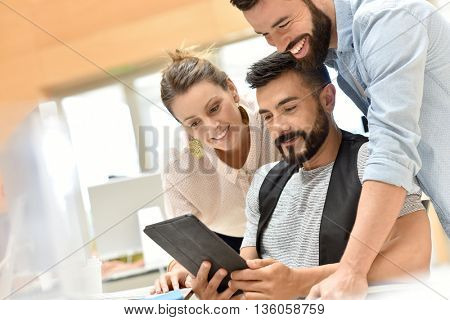 Team of cheerful designers working with tablet