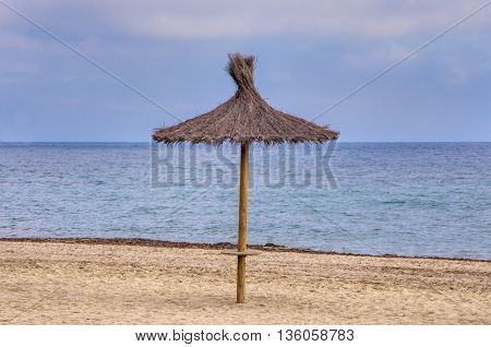 Straw sunshade tranquil sea blue sky. Lonely mediterranean beach. Summer travel destination.