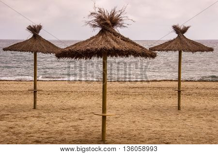 Three straw sunshades tranquil sea evening sky. Lonely mediterranean beach. Summer travel destination.