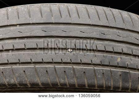 A flat tire by a little long screw