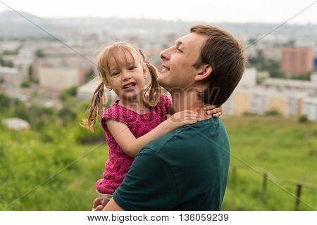 Father and daughter walking on a hill. He is holding her in his hands. Both look happy.
