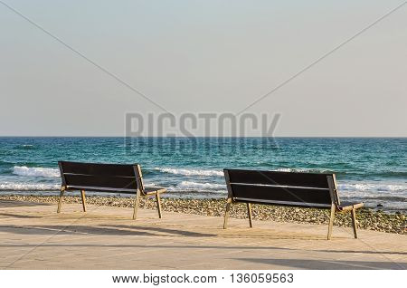 Two empty benchs overlooking Mediterranean sea. Horizontal.