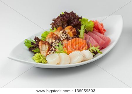 Salmon, Eel And White Fish With Wasabi, Ginger, Sesame And Lettuce On A White Plate