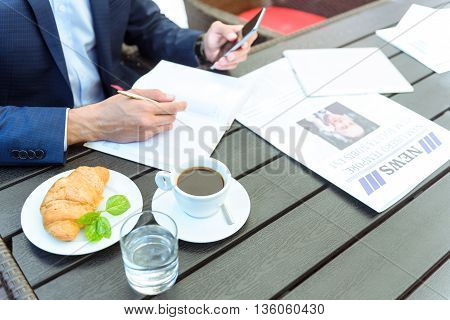 Close up of male hands making notes into a notebook. Businessman is sitting in cafe and using mobile phone. Focus on cup of coffee and croissant on table