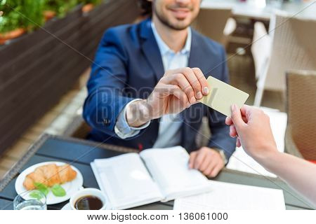 Take this for payment. Confident young man is giving credit card to waiter in restaurant. He is sitting at table and smiling. Focus on their hands